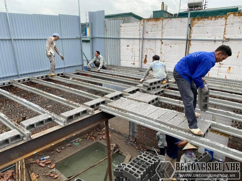 Hình ảnh công nhân đang lắp từng viên gạch Block nhẹ vào hệ dầm ứng lực tại nhà anh Trung, Tây Hồ